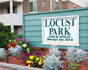 'Locust Park' sign and flowers at entrance                             to complex